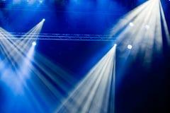 Blåa ljusa strålar från strålkastaren till och med röken på teatern eller konserthallen Belysningsutrustning för en kapacitet ell arkivfoton