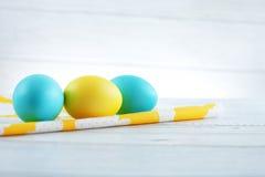Blåa och gula ägg på tyget Begreppet av en lyckliga Easte Royaltyfri Foto