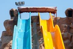 Blåa och gula aquaparkglidbanor Arkivbild