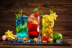 Blåa och gula mojitos för förkylning Röd mojito med mintkaramellen Mojito med rom Alkohol på en träbakgrund Sommardrinkar och coc arkivbild