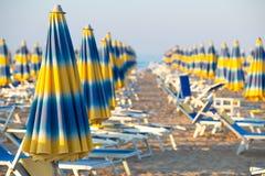 Blåa och gula paraplyer på stranden royaltyfri foto