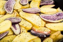 Blåa och gula potatisar i en kastrull Arkivbild