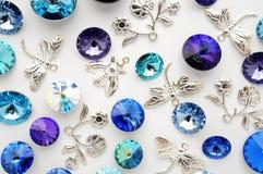 Blåa och purpurfärgade kristaller och metallbin och blommor och sländor på vit bakgrund Royaltyfria Bilder