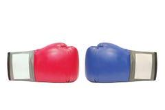 Blåa och röda boxninghandskar i vit bakgrund Royaltyfria Foton