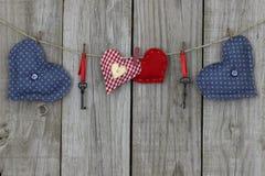 Blåa och röda hjärtor som hänger på klädstreck Arkivbilder
