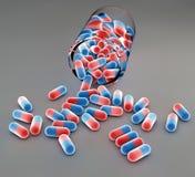 Blåa och röda preventivpillerar och flaska Royaltyfri Bild