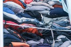 Blåa och röda toner av kläder i en kvinnas garderob, vikta men som är smutsiga, i behov av den hemliga organisationen Visa do royaltyfri bild