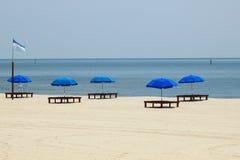 Blåa paraplyer på stranden Arkivfoto