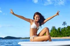 blåa pojkeskrivbordflickor ser sittande surfa för havet Lycklig sund kvinna i havet Loppsemester Lifest arkivfoton