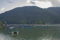 Blåa röda gula gröna gamla träfartyg och katamaran på vattnet ekor på sjön mot bakgrunden av gräsplan royaltyfri foto