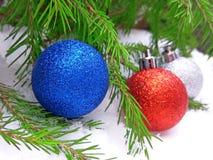 Blåa, röda och för silver för nytt år bollar med det gröna granträdet på snöig bakgrund arkivfoto