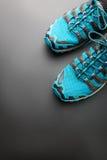Blåa rinnande skor på grå färger Royaltyfri Bild