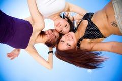 blåa roliga flickor som har soligt under för sky Arkivbild