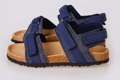 Blåa sandaler för ungar som isoleras på vit bakgrund arkivfoto