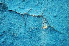 Blåa skalningsmålarfärg och skrapor på väggen av ett hus, slut upp Arkivfoton