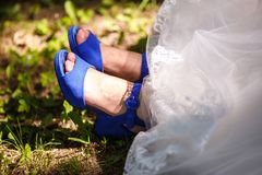Blåa skor på foten av bruden i en vit klänning royaltyfria foton