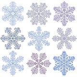 Blåa snöflingor på en vit bakgrund Royaltyfria Bilder