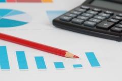 Blåa stångdiagram med räknemaskinen och blyertspennan Arkivfoton