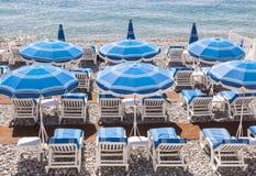 Blåa strandparaplyer i Nice Arkivbild