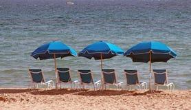 Blåa strandstolar med paraplyer arkivfoto
