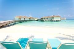Blåa strandstolar på vit sand med träbryggan och tropiska villor i Maldiverna på bakgrund, tropiskt feriebegrepp fotografering för bildbyråer
