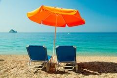 Blåa sunbeds och orange paraply (slags solskydd) på paradisstranden in Royaltyfria Bilder
