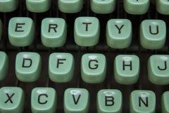 Blåa tangenter av en gammal skrivmaskin med svarta bokstäver tätt upp royaltyfri bild