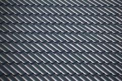 Blåa texturerade tegelplattor som täcker taket arkivfoto