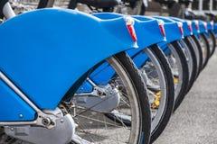 Blåa uthyrnings- cyklar i rad fotografering för bildbyråer