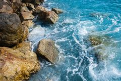 Blåa vågor bryter på vaggar av kusten royaltyfri foto