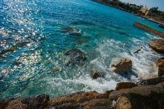Blåa vågor som kraschar mot, vaggar av stranden royaltyfri fotografi