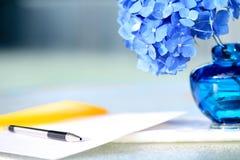 blåa vanlig hortensiamaterial bredvid writing Arkivbild