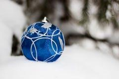 Blåa xmas-prydnader på snöig bakgrund Royaltyfri Foto