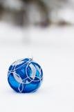 Blåa xmas-prydnader på snöig bakgrund Royaltyfria Bilder