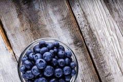 Blåbär i en glass krus på trätabellen Fotografering för Bildbyråer