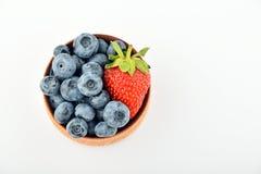Blåbär och en jordgubbe i träbunken som isoleras på vit Arkivfoto