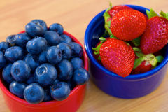 Blåbär och jordgubbe i cans Arkivfoton