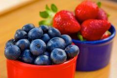 Blåbär och jordgubbe i cans Arkivbilder
