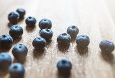 Blåbär som strilas med socker på trädiskbänken Royaltyfri Bild