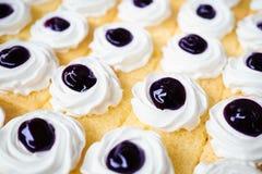 blåbärkaka Breda smör på kakan med blåbärsås och piskaCR royaltyfri bild