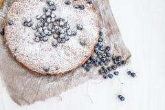 Blåbärkaka med nya blåbär och sockerpulver på en beig Fotografering för Bildbyråer