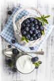 Blåbärkorg och exponeringsglas av yoghurt på den vita trätabellen Royaltyfria Foton