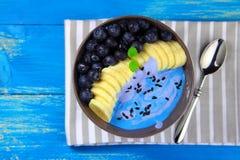 Blåbärsmoothie med en banan i en rund bunke royaltyfri fotografi