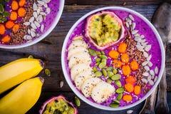 Blåbärsmoothies bowlar med hav-buckthornen, bananen, passionfrukt, chiafrö, pumpafrö, solrosen och linfrö royaltyfri foto