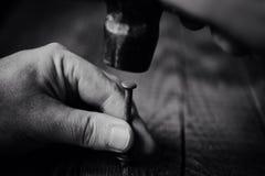 Blåsa en hammare spikar på, arbete av förlagen Fotografering för Bildbyråer