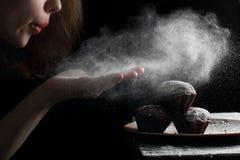 Blåsa pudrat socker med händer på muffierna Arkivfoton