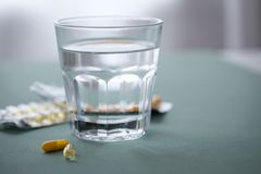 Blåsa två av gul pillerminnestavlamedicin med exponeringsglas av vatten royaltyfria foton