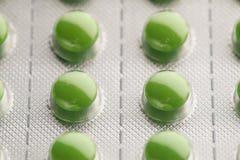 Blåsapacke med gröna preventivpillerar Royaltyfri Foto