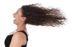 Blåsigt: profil av att skratta kvinnan med att blåsa hår i vindisola royaltyfri fotografi