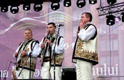 Blåsinstrumentaktörer har gyckel som spelar musik i de moldaviska nationella dräkterna royaltyfri foto
